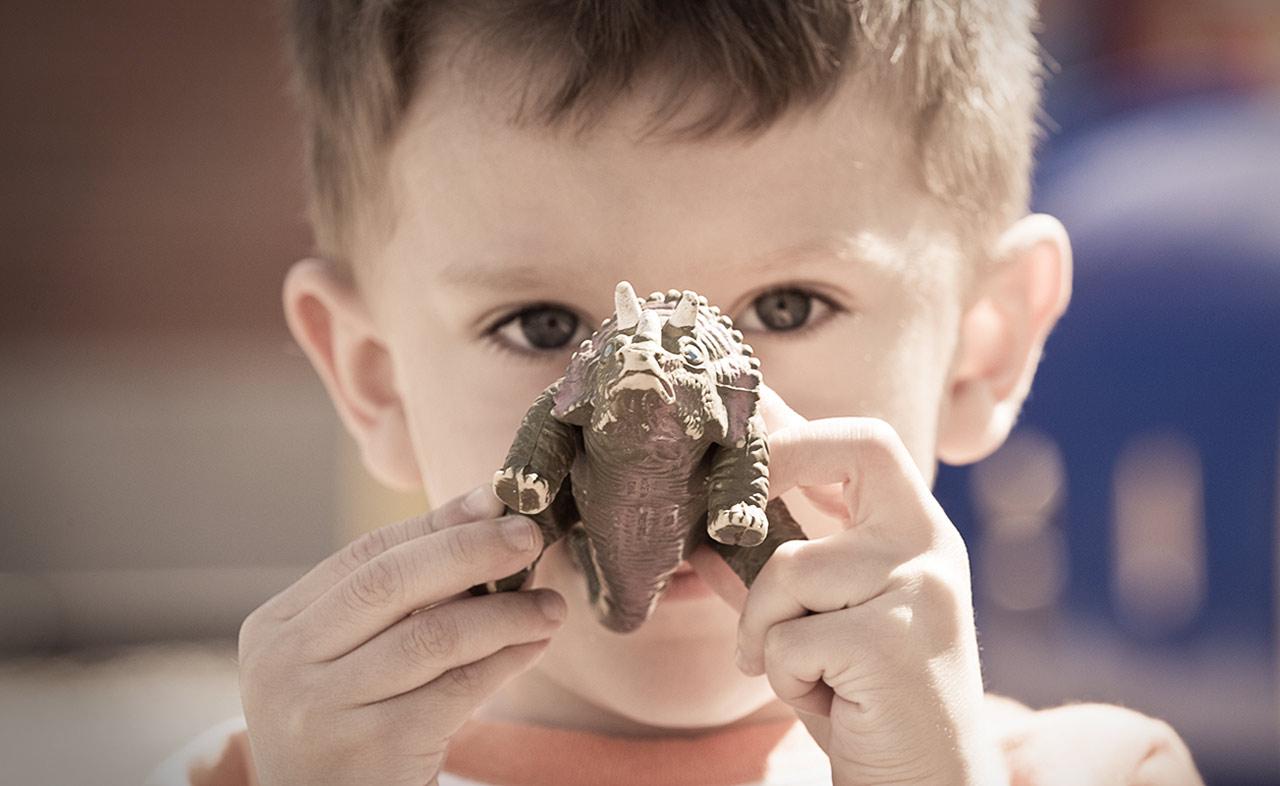 Boy Holding a Dinosaur